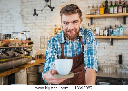 Smiling attractive bearded barista serving you cup of coffee on wooden coaster in cafe