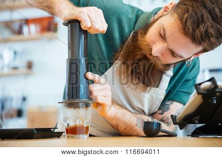 Barista preparing coffee with press in coffee shop