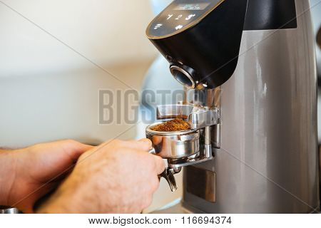Closeup portrait of barista grinding coffee