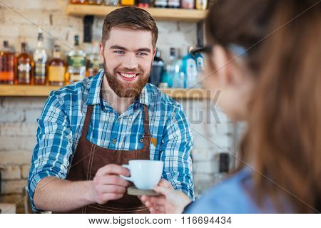 Cheerful attractive bearded barista serving cup of coffee to customer