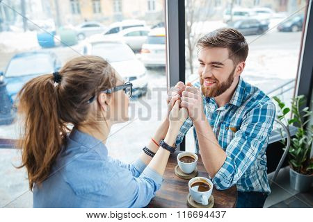 Happy young couple on a date drinking coffee and holding hands in cafe
