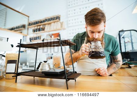 Barista smelling coffee in coffee shop