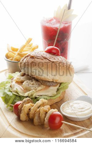 Delicious Hamburger And French Fries And Onion Rings On Wooden Background