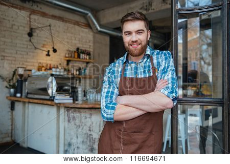 Smiling handsome young waiter in brown apron standing in cafe with hands folded