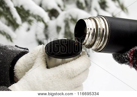 Hot tea in a thermos outdoor in winter