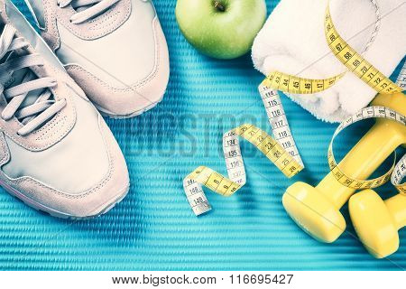Fitness Frame With Dumbbells, Sneakers And Green Apple . Healthy Lifestyle Concept