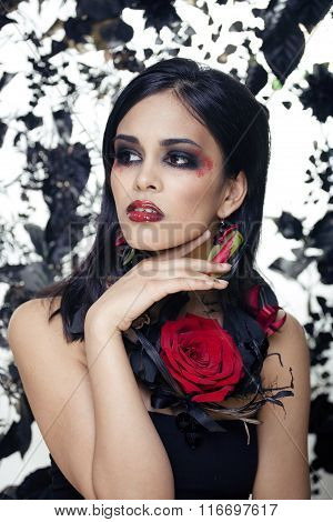 pretty brunette woman with rose jewelry, black and red, bright make up kike a vampire closeup red li