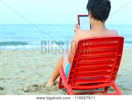 Boy Reads An Ebook On Red Chairs