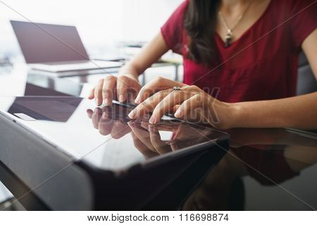 Woman Using Tablet Computer For Daily Work In Office