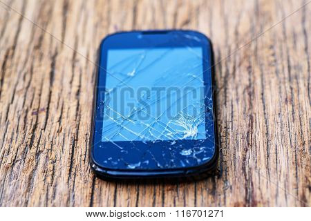 Cracked Mobile Smartphone On Wooden Background, damage mobile phone