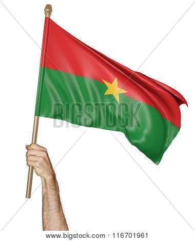 Hand proudly waving the national flag of Burkina Faso