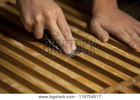 Male hands using tool to remove excess varnish