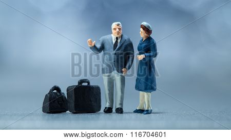 Miniature people - a couple waiting in the airport lobby