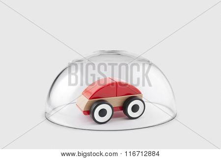 Red toy car protected under a glass dome