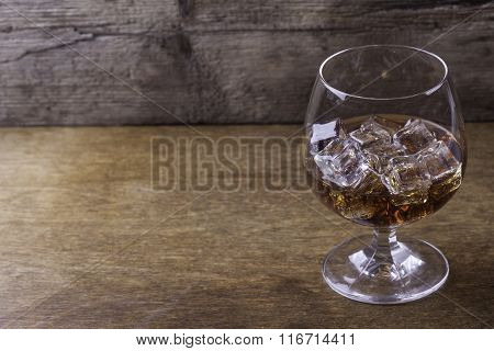 cognac in a glass with ice  on wooden background closeup