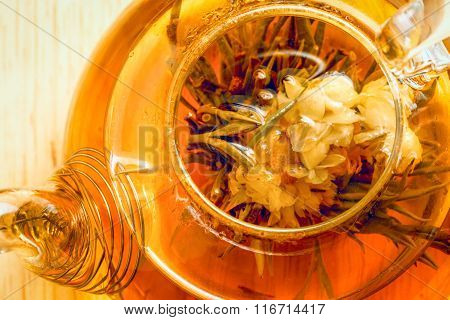 A Glass Tea Pot With Flower Chinese Tea Top Close Up View