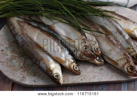 Raw vendace fish on a marble cutting board with green onion