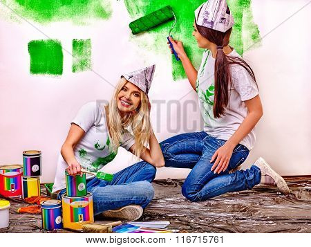 Happy two women friends painting wall at home.