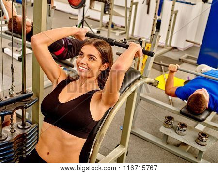 Group of people working with dumbbells his body at gym. Young woman hard working on foreground.