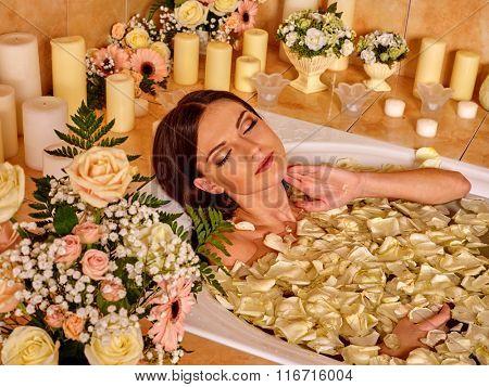 Woman applying luxury bath with rose petals at bathroom.