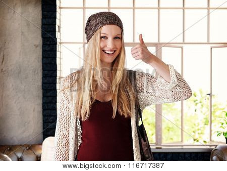 Attractive blonde woman showing thumbs up sign, smiling happy.