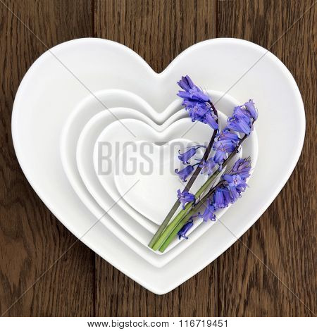 Heart shaped porcelain dishes with bluebell flowers over old oak background.