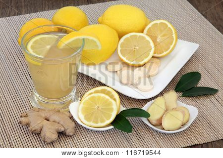 Antioxidant natural cold remedy relief drink with lemon fruit, vitamin c tablets and ginger spice on bamboo over oak background.