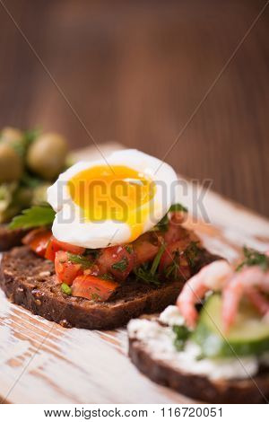 Tasty snack of open sandwich with tomato and soft boiled egg on wooden cutting board