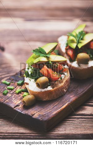 Tasty snack of open sandwich with avocado and soft cheese on wooden cutting board.