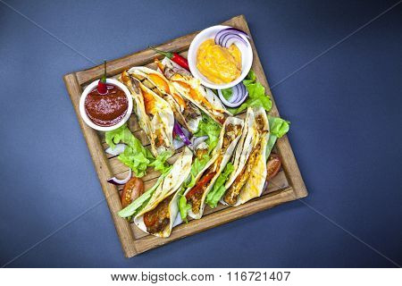 Mexican Tortilla with meat, beef and stewed vegetables and spicy sauce on a wooden tray