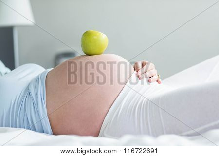 Pregnant woman with apple on belly at home