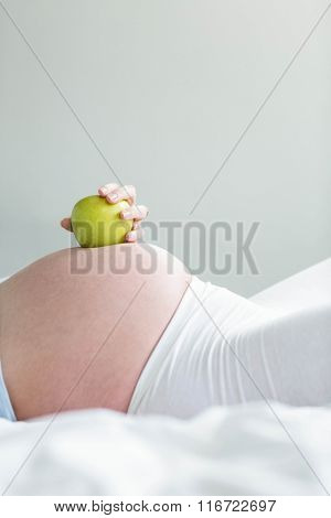 Pregnant woman holding an apple on her belly at home