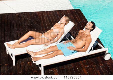 Peaceful couple sunbathing on deck chairs poolside