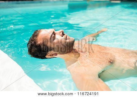 Peaceful man floating in the pool with closed eyes