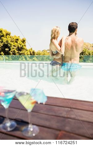 Happy couple in the pool with cocktails on the edge