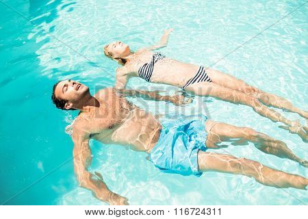 Peaceful couple floating in the pool with closed eyes
