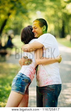 Young And Beautiful, Hipster Couple Hugging In The Park On Holi Color Festival With Colour Paint Pow