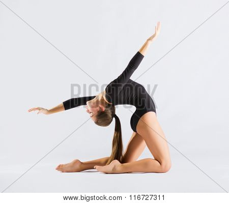 Young girl engaged gymnastic on grey