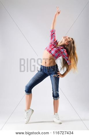 Young modern dancing girl in jeans on grey