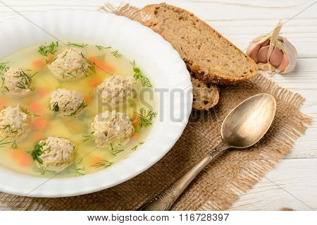 Dietary soup with meatballs and vegetables on white wooden table.