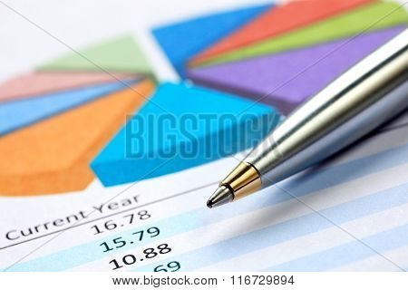 Silver ballpoint pen on pie chart with financial figures.