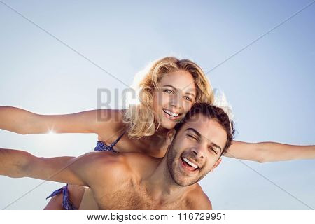 Boyfriend giving piggy back to his girlfriend by the pool