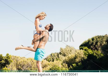 Boyfriend carrying his girlfriend by the pool