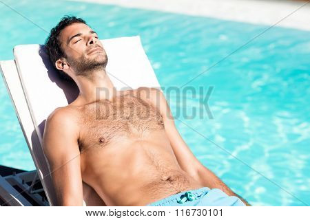 Handsome man resting on deckchair by the pool