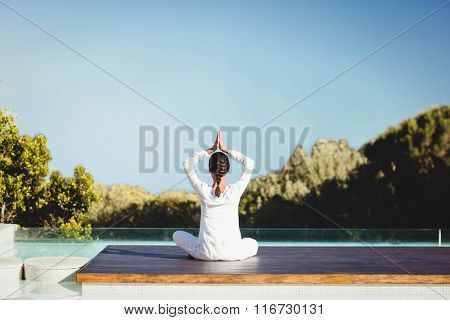 Calm brunette doing yoga by the pool