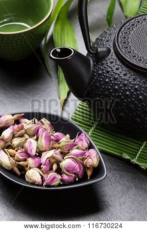 Asian rose tea and teapot over stone table