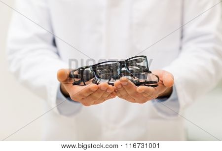 close up of optician with glasses at optics store