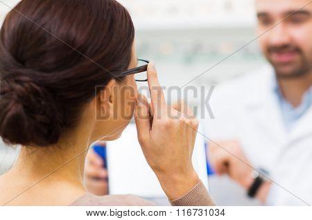 close up of woman choosing glasses at optics store
