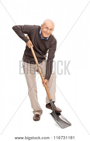 Full length portrait of a senior man digging with a shovel and looking at the camera isolated on white background