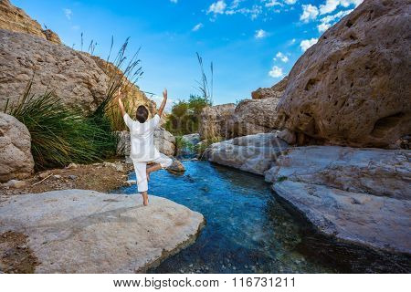 Travel national parks and reserves Ein Gedi, Dead Sea, Israel. Elderly woman practices yoga on small lake